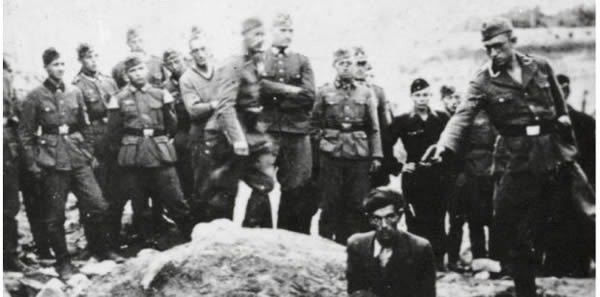 Alleged photograph of an Einsatzgruppen at work. However, this is almost certainly a Soviet forgery, a recreation for the cameras. The 'executioner' is holding a Soviet Tokarev pistol and the uniforms worn are a bizarre mixture – are we to believe that the Einstazgruppen killings were spectated by such a motley collection of soldiery from all kinds of units? Included are a man wearing the tunic of a regimental bandsman with large shoulder pieces and panzer crewmen in their black uniforms.